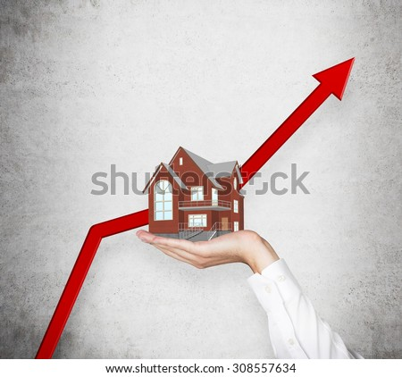 A hand is holding a house. A huge red arrows rocketing as concept of rising real estate market. - stock photo