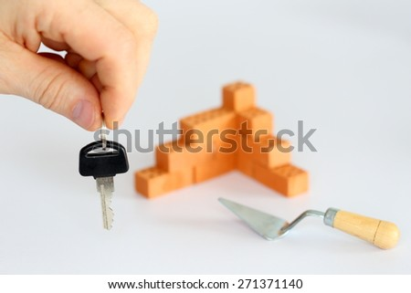 a hand is holding a key with bricks in background - stock photo