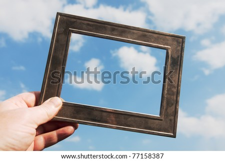 a hand is holding a metal frame against the blue sky