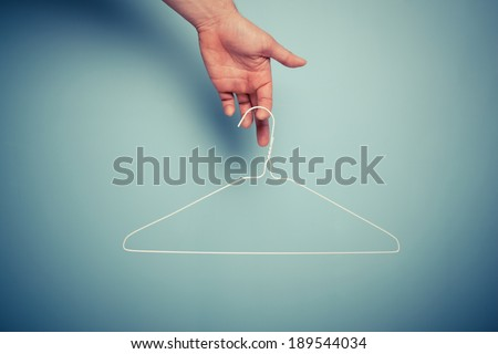 A Hand is holding a wire hanger - stock photo