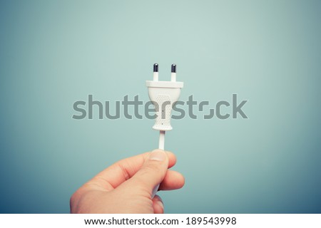 A hand is holding an electric plug - stock photo