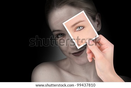A hand is holding up a photo of a young eye on a wrinkled woman's face. She is isolated on a black background. Use to represent time or aging. - stock photo