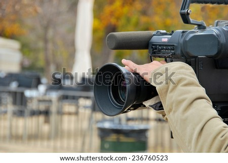 A hand is operating a tv camera
