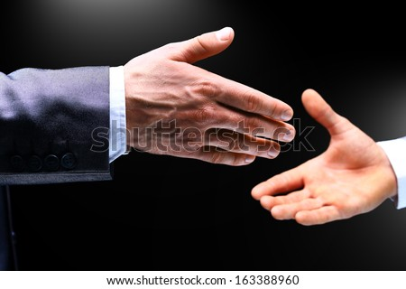 A hand is reaching out or grabbing for help from another hand in dark background - stock photo