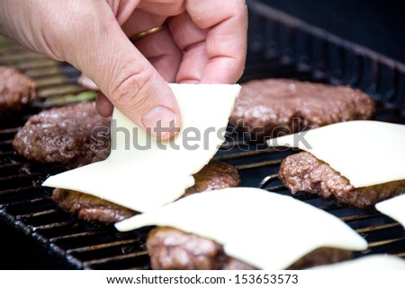 A hand lays out slices of white cheese on freshly grilled hamburgers.
