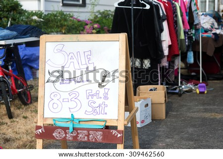 A hand-lettered sign advertises a home garage sale of used items. - stock photo