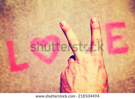 a hand making a peace sign for the letter V in the word love toned with a retro vintage instagram filter effect  - stock photo