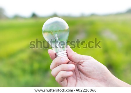 A hand man holding light blub  with green background, eco energy concept - stock photo