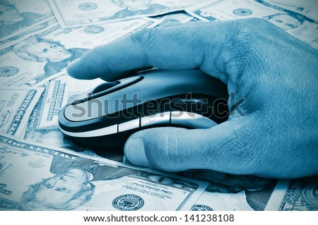 a hand man using a computer mouse on a background full of dollar banknotes, depicting the e-commerce concept or the internet fraud concept - stock photo