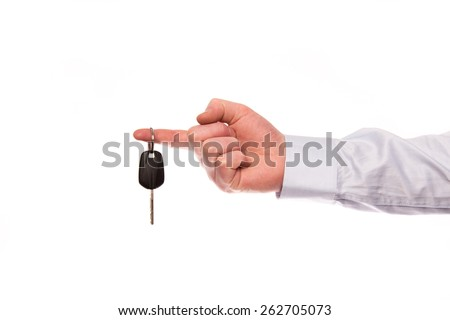 A hand of a businessman hold up a car key isolated on a white background
