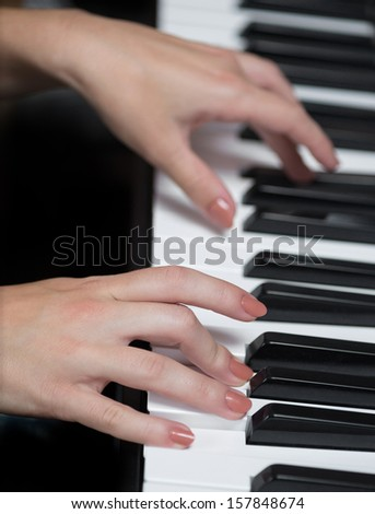 A hand of a girl playing piano. Selective focus. - stock photo