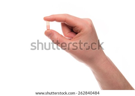 A hand of a man hold a pill between thumb and forefinger isolated on a white background - stock photo