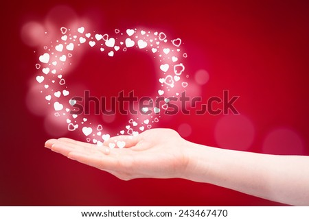 A hand of a young woman gives a heart as a Valentine's Day gift before a red background. - stock photo