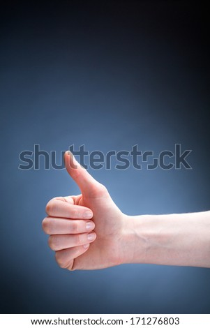 A hand of a young woman giving a thumbs up sign over a dark blue background.