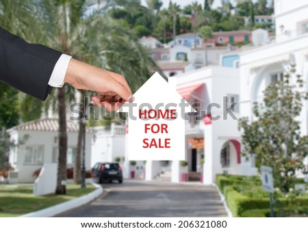 A hand of property agent holding the banner - Home for Sale, real estate sign.
