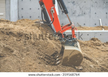 a hand of small back hoe digging the dirt in small area. - stock photo