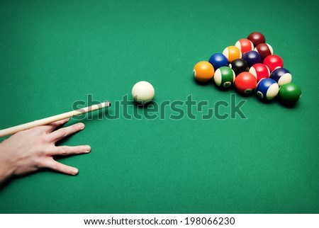 A hand of someone who is playing pool. - stock photo