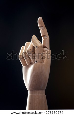 A hand of wood doll, one finger means one(1) and direction to the sky isolated black background at the studio. - stock photo