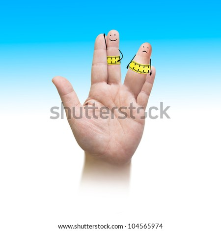 a hand, one finger showing upside. on the finger is paint. it looks like a little person. thin and fat person with measuring tape on the stomach - stock photo