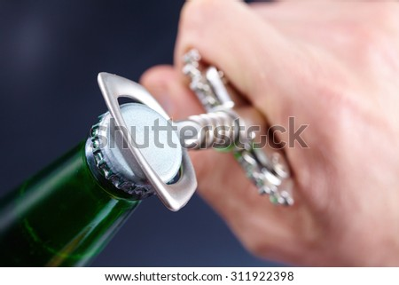 A hand opening a bottle of beer - stock photo