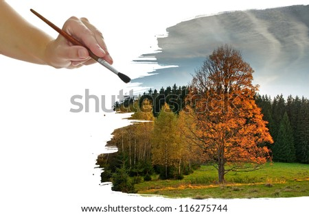 a hand painting an autumnal landscape with a big tree - stock photo