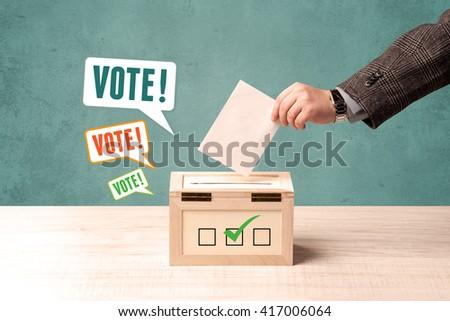 A hand placing a voting slip into a ballot box - stock photo