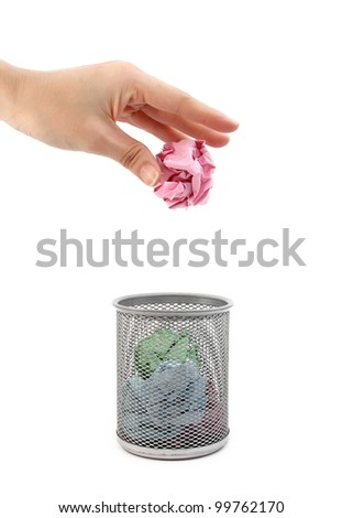 A hand placing paper in trash can on white background - stock photo