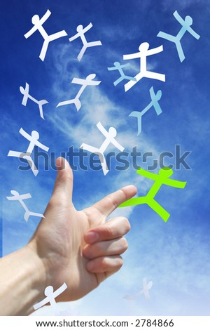 A hand pointing to a paper man falling from the sky - stock photo