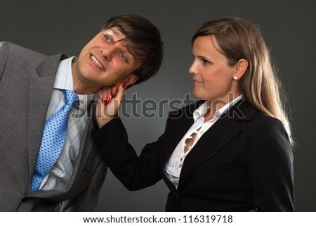 a hand pulling a businessman ear on gray - stock photo