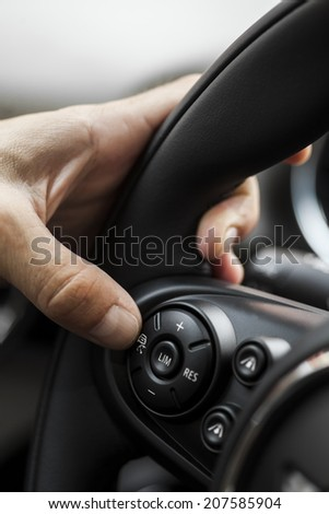 A hand pushes the cruise control button on a steering wheel. - stock photo