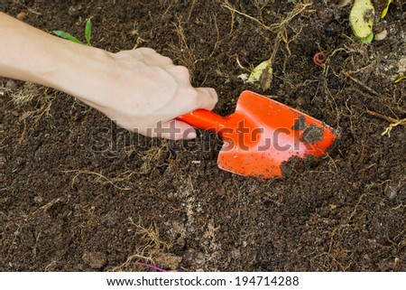 A hand pushing a dirty trowel into the earth - stock photo