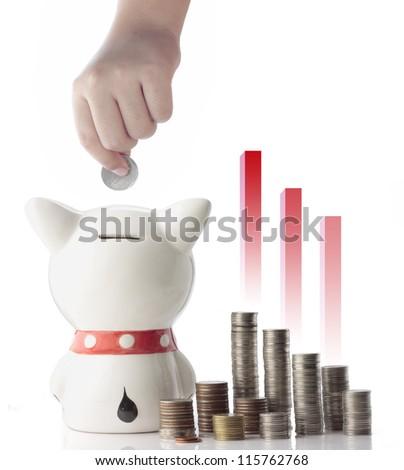 a hand saving coin in piggy bank - stock photo