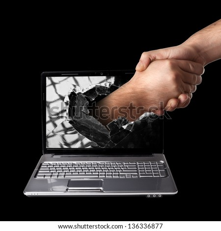 A hand scomes right out of the laptop screen to shake hands CONCEPT. isolated on black background High resolution