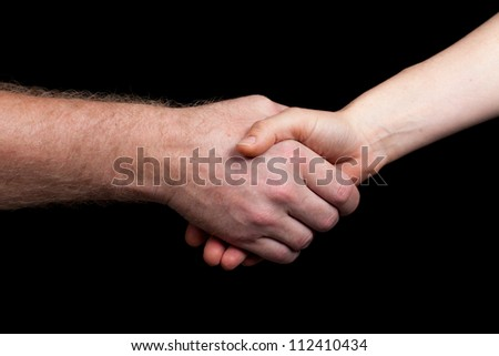 A hand shake between a man and woman. Isolated over black - stock photo