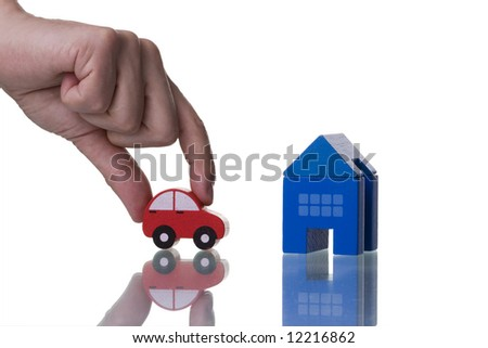 a hand showing a house and a car isolated with reflection - stock photo
