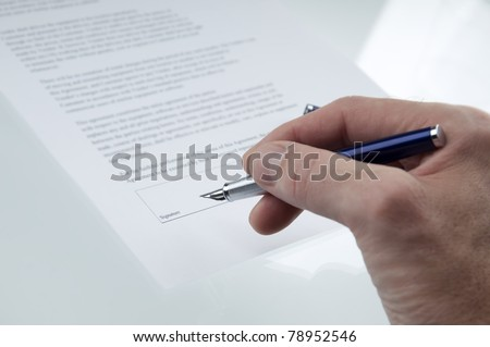 A hand signing a business contract - stock photo