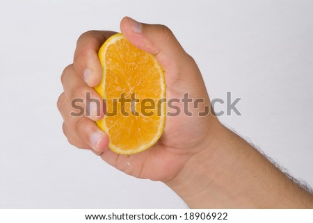 A hand squeezing for orange drops
