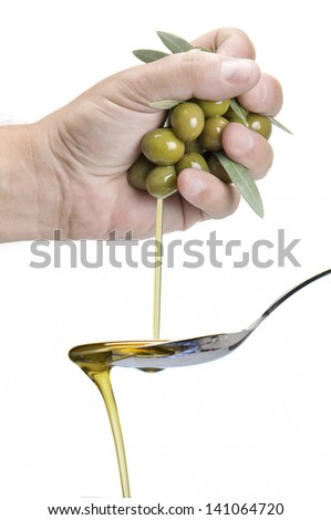 A hand squeezing olives and getting olive oil into a spoon. - stock photo