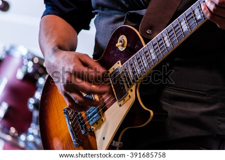 A hand strums at electric guitar strings in front of the blurred background of a drum kit as a lead guitarist plays a chord - stock photo
