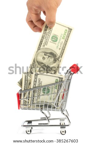 A hand taking one hundred US dollar bill out of a shopping cart, isolated on white background.
