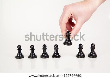 a hand taking pawn from the row - stock photo