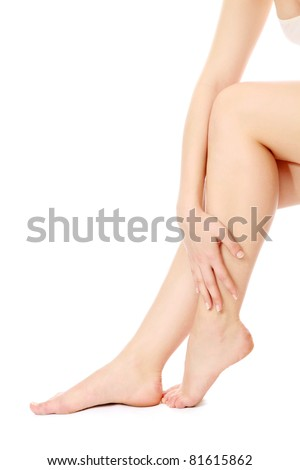 A hand touching beautiful woman's legs, isolated on white - stock photo