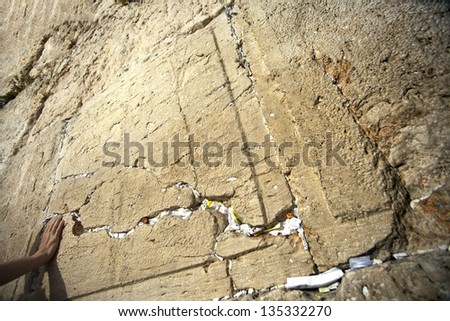 A hand touching the holy Wailing Wall, looking for comfort and support. The Wailing Wall is one of the most sacred places to the Jewish people - the Wailing Wall in the old city of Jerusalem, Israel. - stock photo