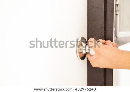 A hand trying to open the door by holding the doorknob with a white copy space on the door.