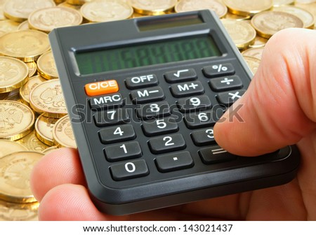 A hand with a calculator on the background of coins on the plane.