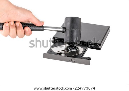 a hand with a hammer destroying a CD-ROM Drive - stock photo