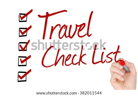 A hand with a marker writing 'Travel Check List'. - stock photo