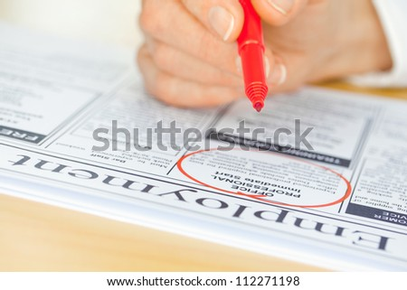 A hand with a pen circling a job in the paper (focus on pen nib and ad)