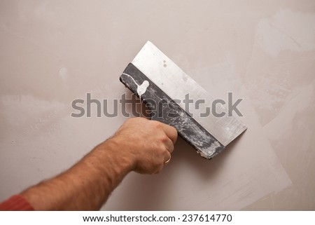 a hand with a spatula, work aligns wall - stock photo