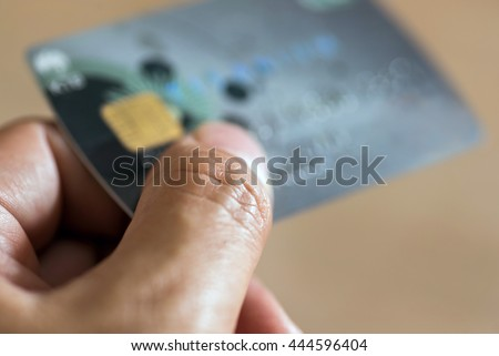 A hand with bank credit plastic card - stock photo